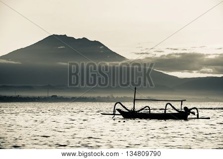 An outrigger canoe achored with a volcano peak above the clouds in the distance.