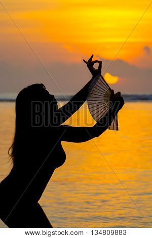 Silhouetted dancer on the beach in Bali with a bright orange tropical sunset in the background.