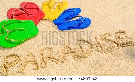 Paradise written in the sand and colored sandals spread into semi circle shape