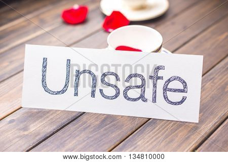 white paper with word unsafe against elegant coffee cup in cafe