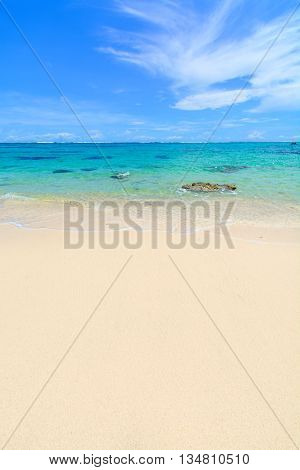 White sandy beach in Bali with aqua coloured water and blue sky all the way to the horizon