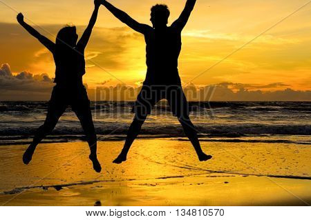 A young couple jumping while holding hands at the beach with a beautiful orange sunset in the background.