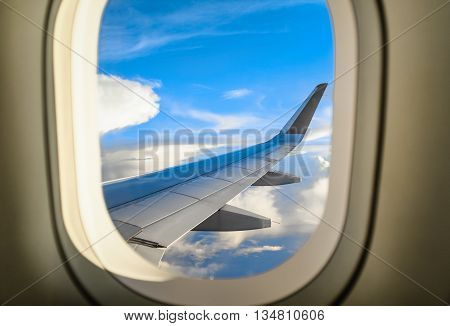 The wing of a plane and clouds as seen from inside a passenger plane.