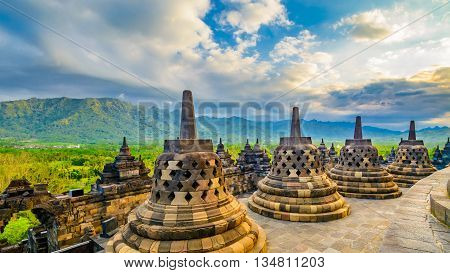 Travel image of 9th century Borobudor Buddhist temple in Indonesia showing the bell shape carvings at the apex of the temple and the tropical surrounding location in the distance.This is a Unesco world hertiage site and popular tourism destination.