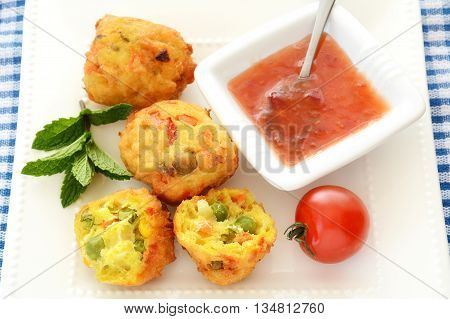 Fresh vegetable pakoras with sweet chili sauce on square white plate on blue and white check cloth in horizontal format