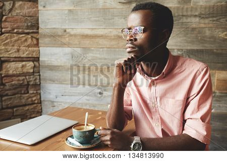 Portrait Of Successful Young African American Journalist Drinking Coffee With Deep-in-thoughts Face,