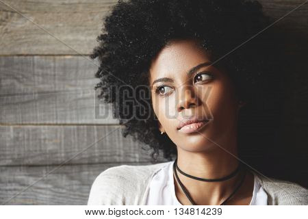 Pretty Young Dark-skinned Female Student With Afro Haircut, Looking Away With Thoughtful And Dreamy
