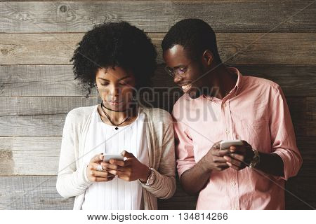African Couple Using Gadgets: Pretty Girl With Afro Hairstyle In Trendy Clothes, Typing A Message On