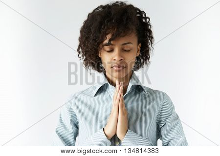Concept Of Meditation And Prayer. African Female Standing In Meditative Pose Against White Wall, Wit