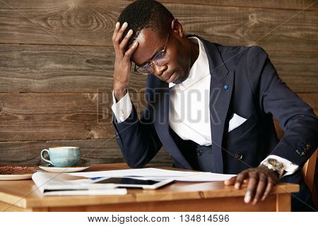 Young African Businessman Looking Puzzled, Having A Computer Problem, Sitting In Deep Thinking Pose,