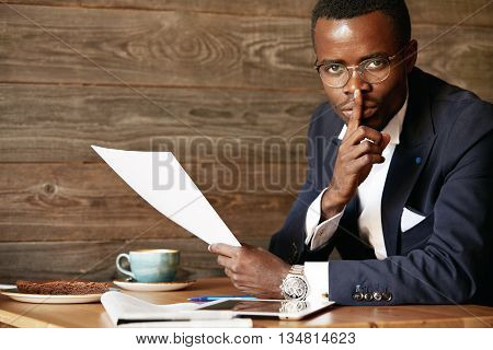 Top Secret. Serious African Businessman In Formal Suit Holding A Finger At His Lips, Saying 'shh', A