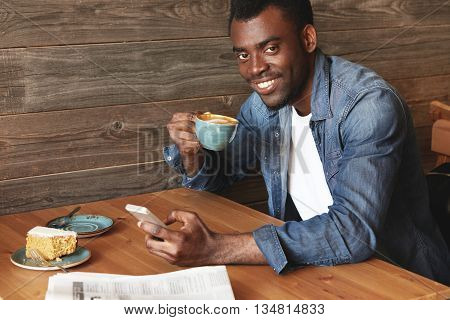 Handsome African American Man Checking Feed On His Device And Drinking Hot Coffee. Young Cheerful Gu