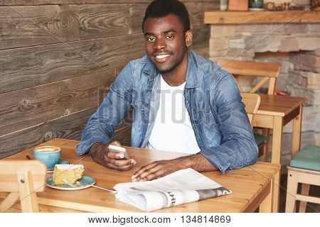 Portrait Of Happy African American Man In Denim Shirt And White T-shirt. Youngster Is Sitting In Caf