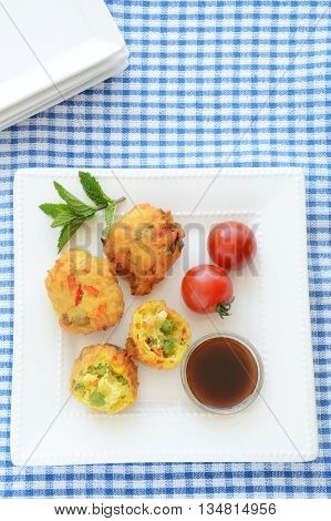 Fresh vegetable pakoras with tamarind chutney on square white plate on blue and white check cloth in vertical format