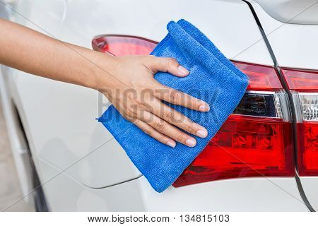 Hand with blue microfiber cloth cleaning taillight white car.