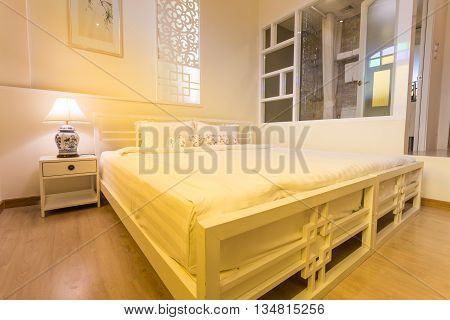 Abstract bedroom in warm light colors. big comfortable double bed in elegant classic bedroom