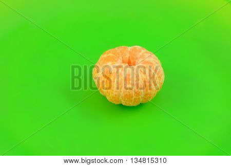 Close up of clementine orange and segments on bright green plate