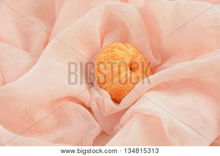 Peeled clementine mandarin orange in folded tablecloth fabric