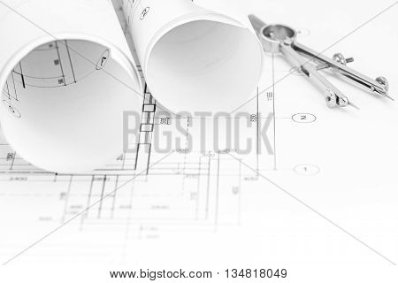 Architectural Blueprint Rolls And Floor Plan With Drawing Copass On Desk