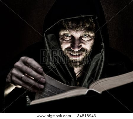 necromancer casts spells from thick ancient book by candlelight on a dark background.