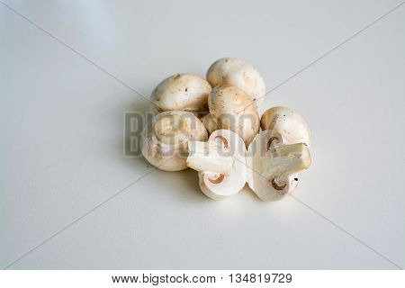 White champignon mushrooms and sliced mushrooms isolated on light background