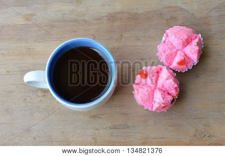 black coffee cup and pink dessert trolley on wooden table