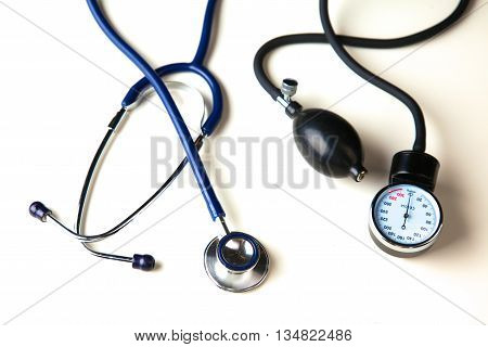 Medical stethoscope and blood pressure cuff on the table.