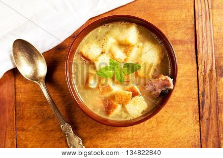 Pea soup with smoked ribs, croutons and spices in a bowl on a wooden background