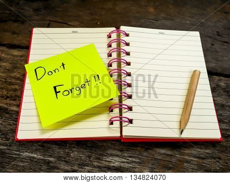 Reminder paper note in note book on wooden table