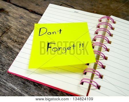 Focus reminder paper note in note book on wooden table