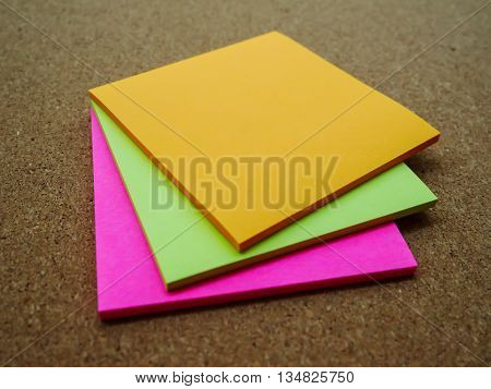 Three color post note on wooden board