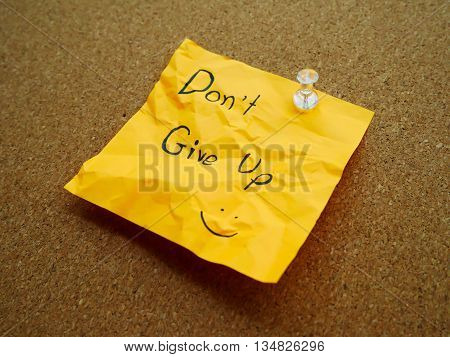 Don't give up in post note on wooden board