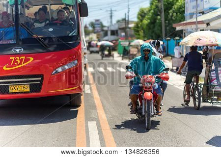 Cebue, Philippines - march 17, 2016: Driver of motobike broke the ruls when crossed double line while overtaking red bus under the hot sun