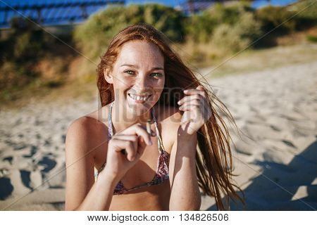 Portrait of redhead woman smoking on the beach.