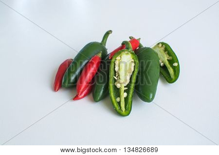 Bright green jalapeno hot peppers and birdseye chilli peppers on white background