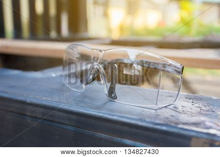 Scratched safety glasses sitting on steel selective focus on scratch marsk with shallow depth of field blurred background with warm sunlight
