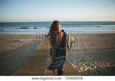 Back view of unrecognizable girl walking on wooden path on beach against of blue sky and sea in windy weather.