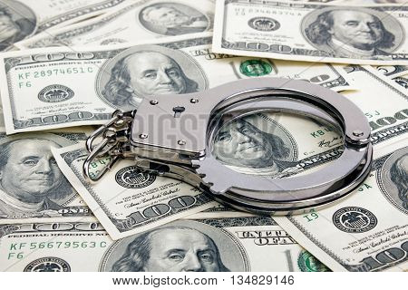 Lot of one hundred dollar bills and handcuffs.