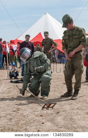 Tyumen Russia - June 11 2016: Race of Heroes project on the ground of the highest military and engineering school. Exhibition of weapon. Visitors of show try on the sapper suit