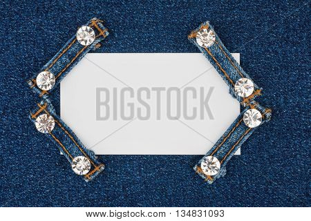 Business card with four straps jeans with rhinestones lies on the light denim with space for your text