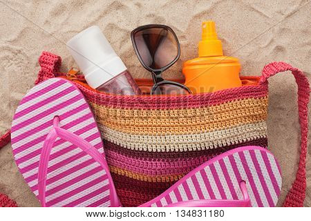 Bag with beach accessories lying on the sand of the beach as a backdrop