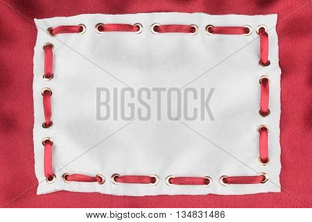 Frame made of white silk with inserted red satin ribbon on red silk background