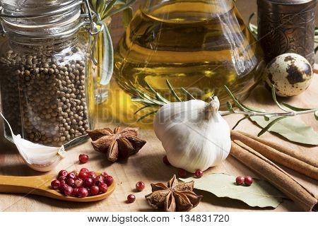 Spices and olive oil on a wooden background