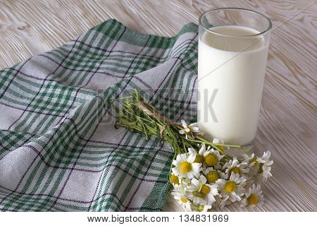 Glass with milk and chamomile flowers on the wooden table