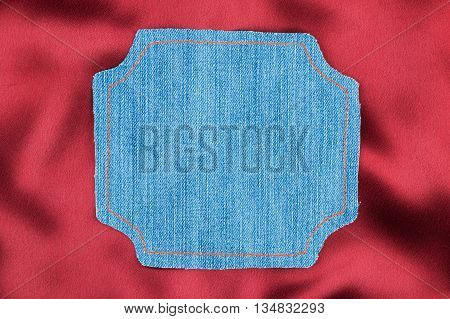 Frame for the text from a blue jeans fabric with the stitched lines of an orange thread on a red silk