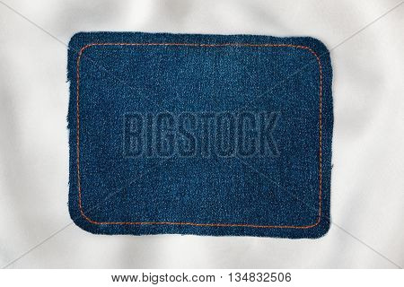 Frame for the text from a blue jeans fabric with the stitched lines of an orange thread on a white silk