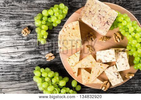 Cheese plate: organic homemade goat cheese with walnuts and spices. Green Grapes and walnuts on an old rustic background studio lights top view