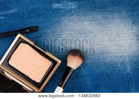 Still life from cosmetics on ragged jeans with place for your text