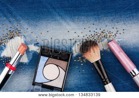 Still life from cosmetics on ragged jeans with rhinestones with place for your text