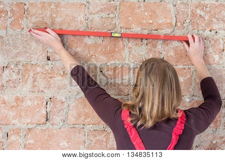 Redhead young woman dressed in red overall is using a spirit level on an old brick wall. Woman is turned back to the camera.